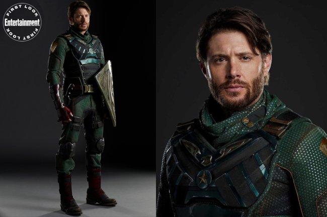 Imagens de divulgação de Jensen Ackles como o Soldier Boy, de The Boys. Ele veste um figurino de super-heróis verde escuro e leva na mão um escudo prata
