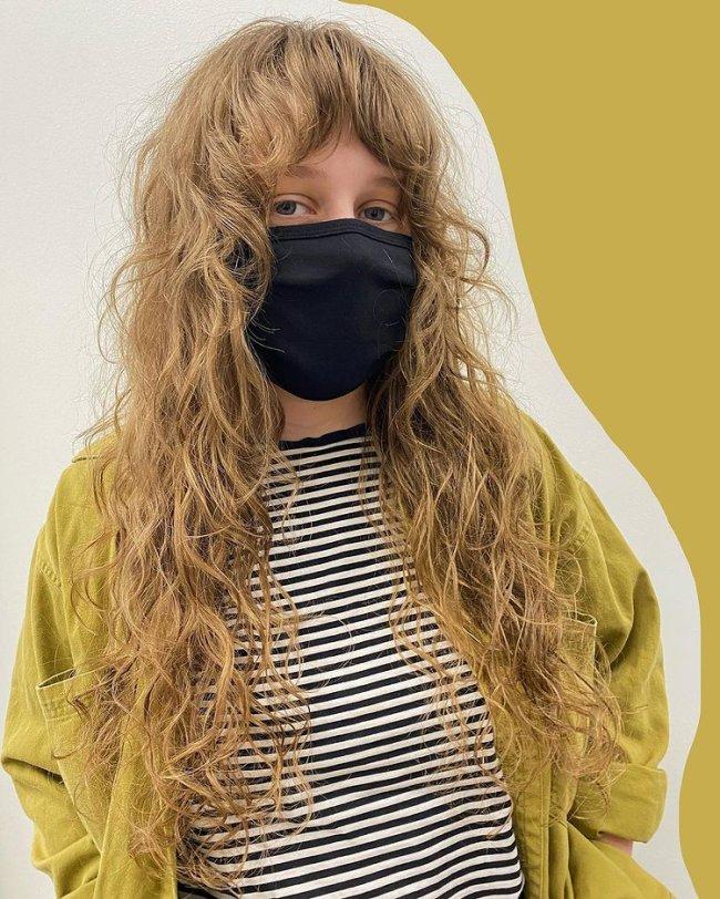 Jovem usando máscara de proteção preta e cobrindo sua expressão facial. Ela veste camisa listrada e blusa verde.