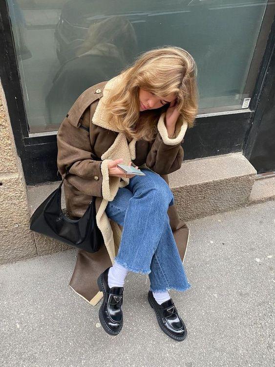 Jovem sentada com a mão apoiada na cabeça, ela olha para o chão, e usa calça jeans com lavagem clara.