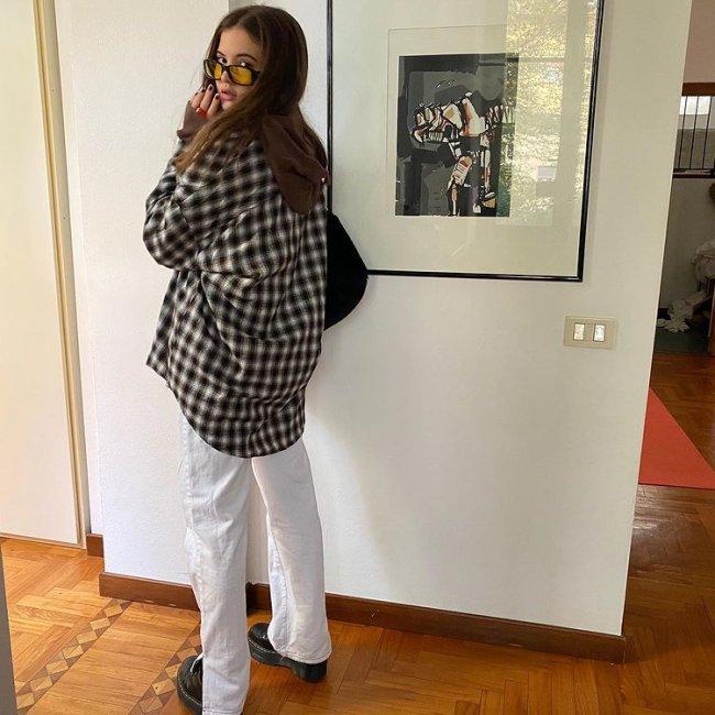 Foto de uma mulher em frente a uma parede de uma casa com um quadro. Ela usa uma camisa xadrez oversized, calça branca, coturno e óculos de sol de lente amarela. Ela está de lado, olha para a câmera e não sorri.