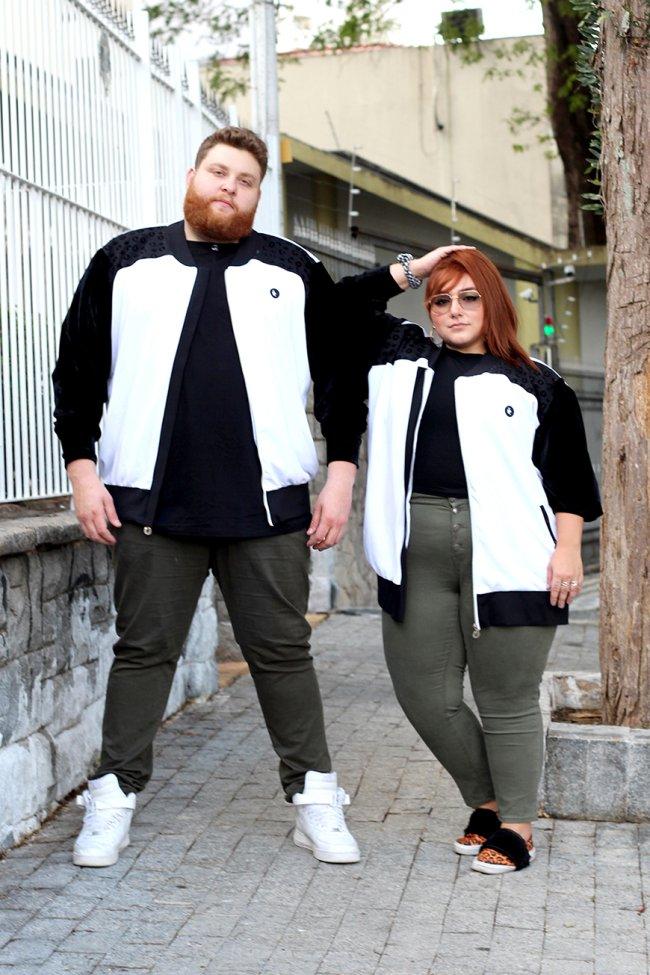 Casal posando na rua com blusa de frio preto e branca igual, camiseta preta igual, e calça verde militar igual. Os dois estão com aparência séria.
