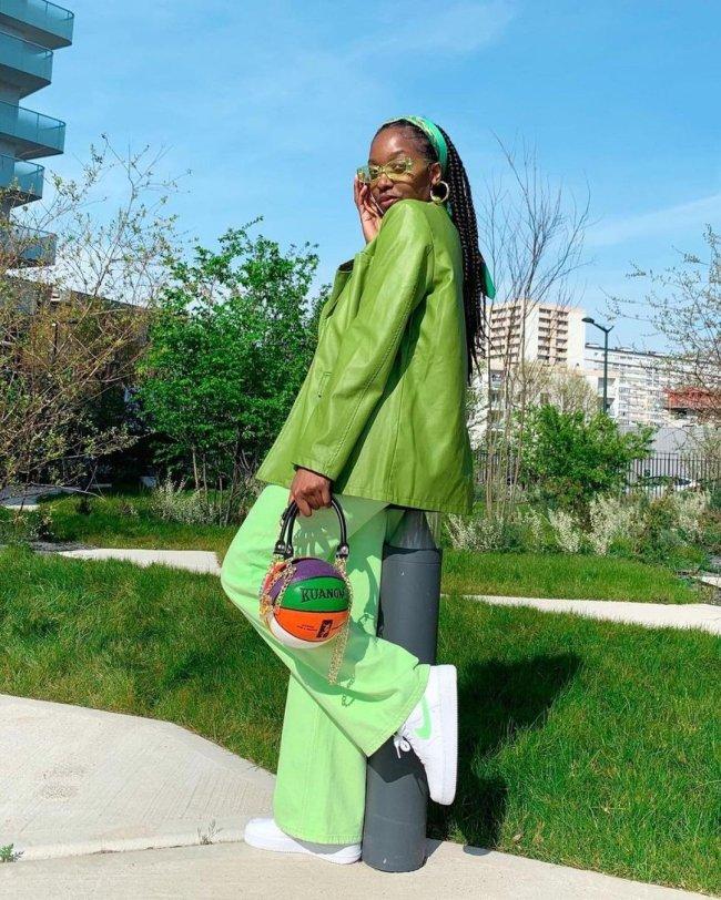 Foto de uma mulher em um parque. Ela usa um casaco verde, uma calça verde, tênis branco e bolsa em formato de bola de basquete. Ela está virada de lado, com a perna esquerda levemente levantada, está com a mão direita segurando o óculos verde no rosto, olha para a câmera e não sorri.