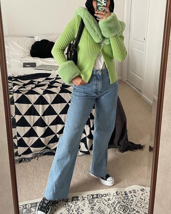 Selfie no espelho de uma mulher. Ela usa um casaco verde menta de pelinhos, calça jeans reta, tênis preto com branco e bolsa preta. O rosto dela não aparece na foto.