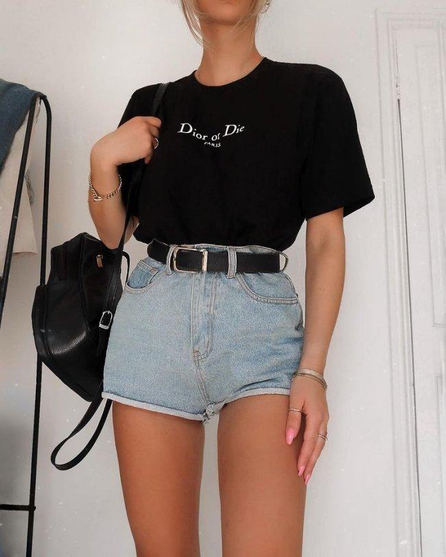 Foto do look de uma mulher. Ela usa camiseta preta, short jeans com cinto preto e mochila preta.