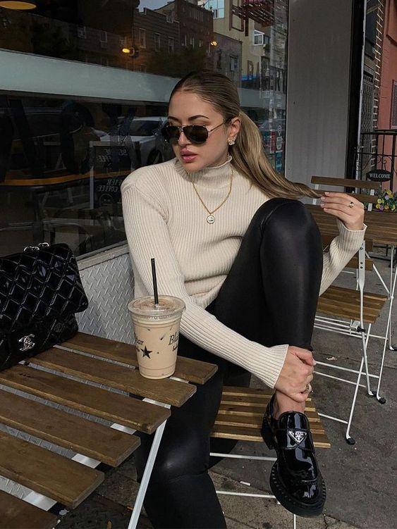 Jovem sentada olhando para o lado com expressão séria, ela está sentada em uma cadeira de madeira, em sua frente tem uma mesinha de madeira e ela usa blusa bege de gola alta e legging preta com mocassim preto.