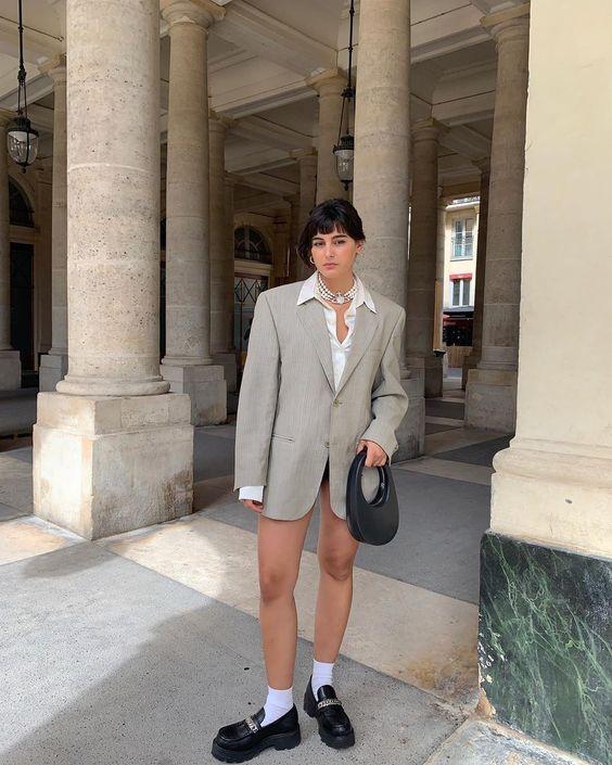 Jovem com expressão séria, posando em frente a colunas, usando blazer alongado cinza, camisa branca, e mocassim preto.