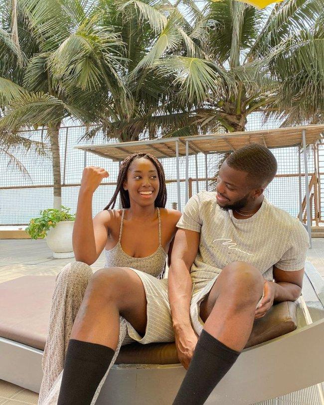 Casal sorridente sentado, atrás podemos ver coqueiros. Eles usam roupas no mesmo tom de bege. A menina usa um vestido e o menino camiseta e short.