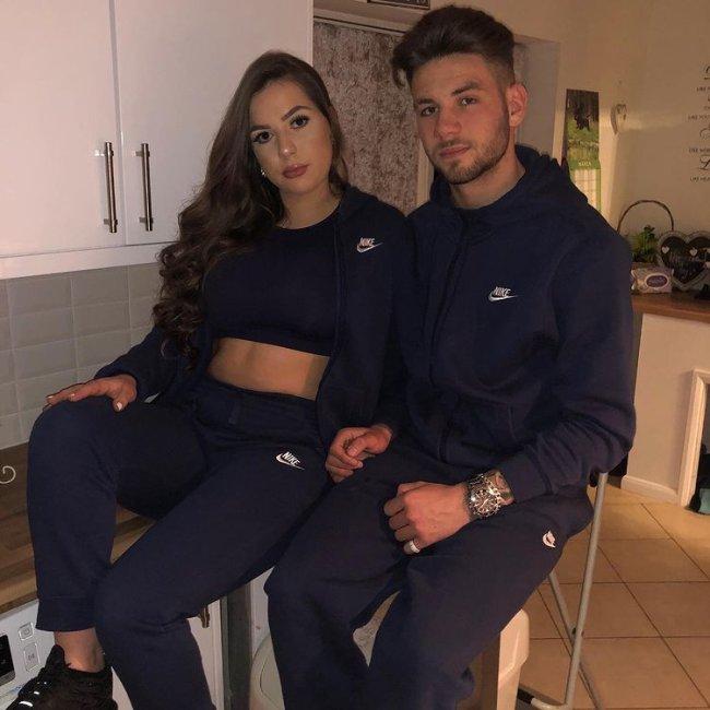 Casal sentado em bancos na cozinha, usando roupas parecidas. A menina usa top preto, blusa de moletom e calça preta. O menino usa blusa e calça de moletom. Os dois estão com uma expressão séria.