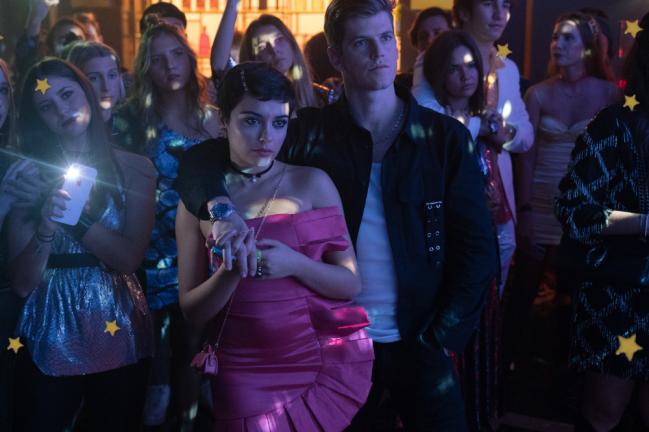Foto com close nos personagens Guzman e Ari, em festa no seriado Elite. Eles estão com uma expressão séria.