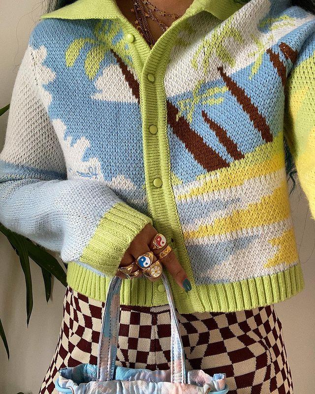 Foto dos detalhes do look de uma mulher. Ela usa um cardigan com estampa divertida, calça com estampa xadrez, anéis divertidos e segura uma bolsa.
