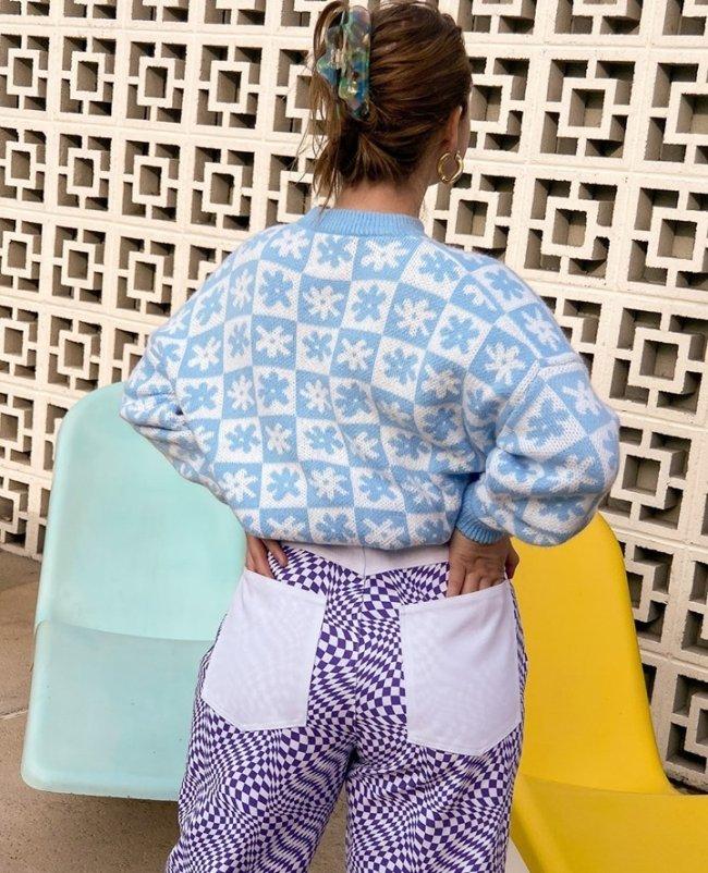 Foto de uma mulher de costas. Ela usa um cardigan branco com estampa azul, calça com estampa psicodélica em um azul mais escuro.