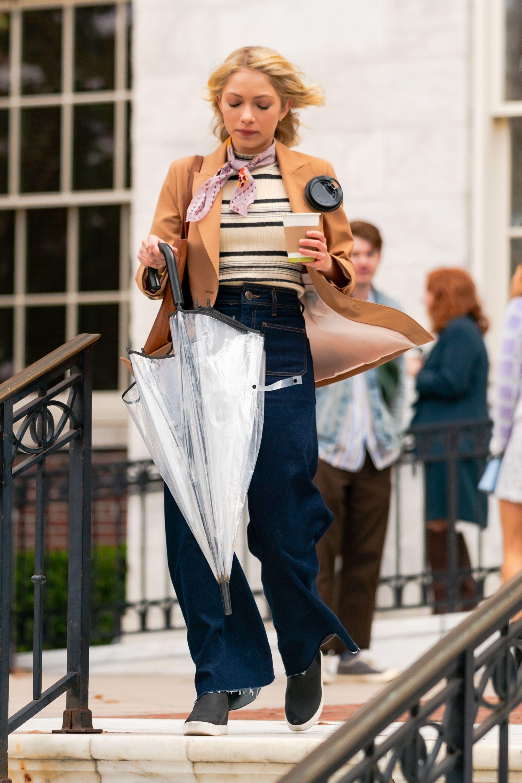 A atriz Tavi Gevinson gravando o reboot de Gossip Girl. Ela está usando uma blusa listrada, jaqueta marrom, calça jeans e tênis preto. Está descendo degraus enquanto segura um café com uma mão e um guarda-chuva com a outra.