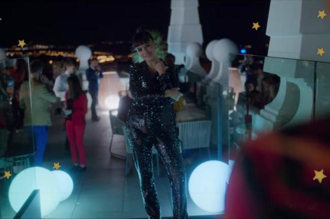 Foto com foco na personagem Mencía com conjunto preto com glitter. Ela está sorridente em meio a um bar.