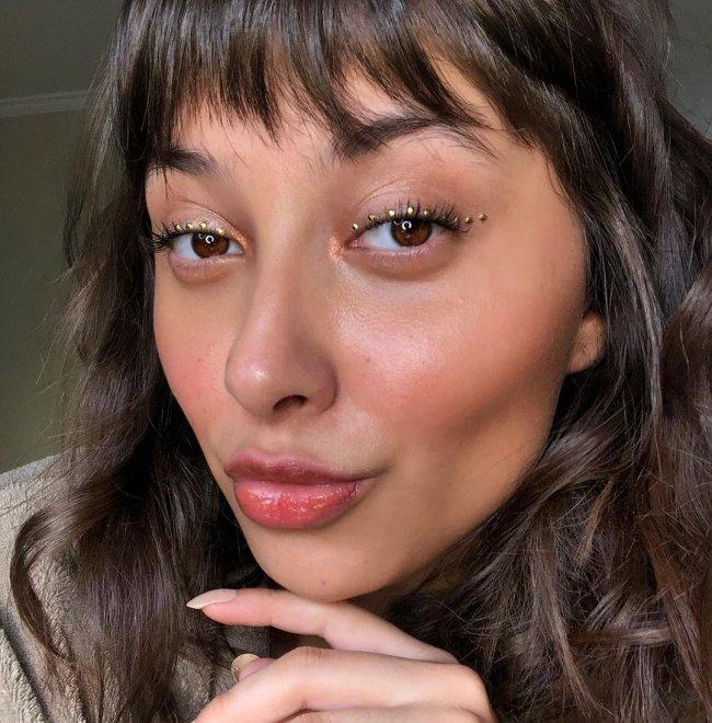 Jovem fazendo biquinho para selfie, com expressão levemente sorridente, usando strass nos olhos e pele com pouca maquiagem.