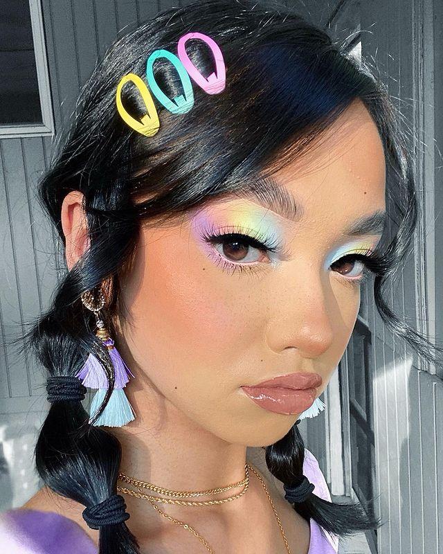 Foto de uma mulher. Ela usa o cabelo em um penteado bolha, com presilhas coloridas de cabelo, maquiagem com gloss, pele natural e sombra com mix de cores em tons pastel. Ela olha para a câmera e não sorri.