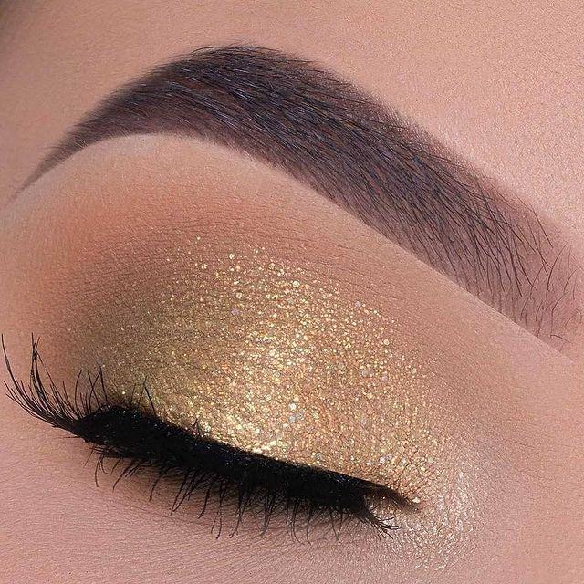 Foto com foco em um olho fechado exibindo a sombra dourada.