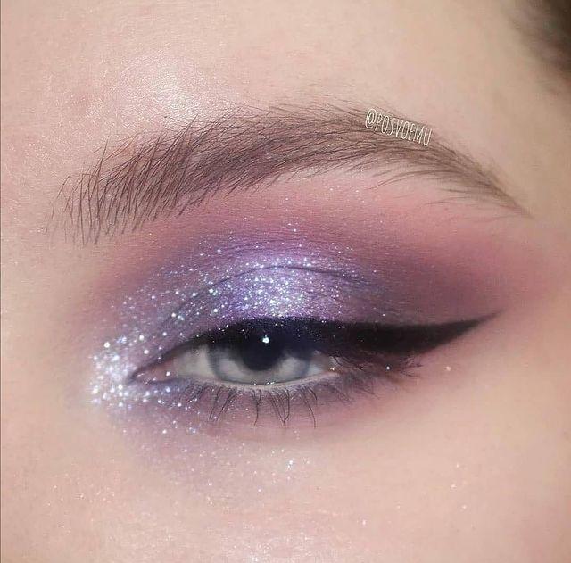 Foto com foco em olho azul aberto, com delineado preto e sombra lilás com canto interno do olho iluminado.