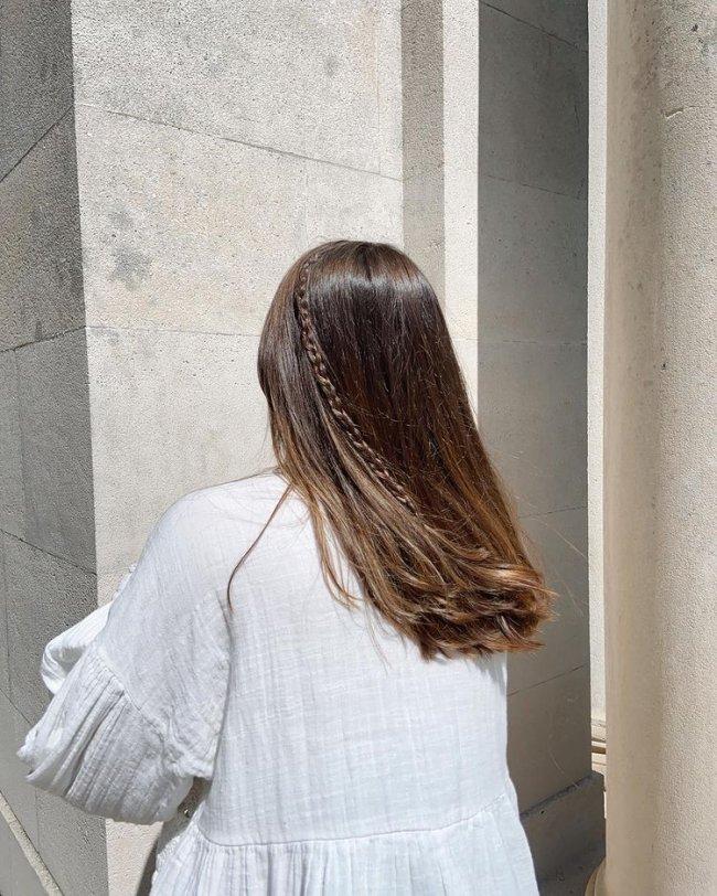 Foto de uma mulher de costas com uma mini trança no cabelo. Ela usa uma blusa branca e está com o cabelo liso solto.
