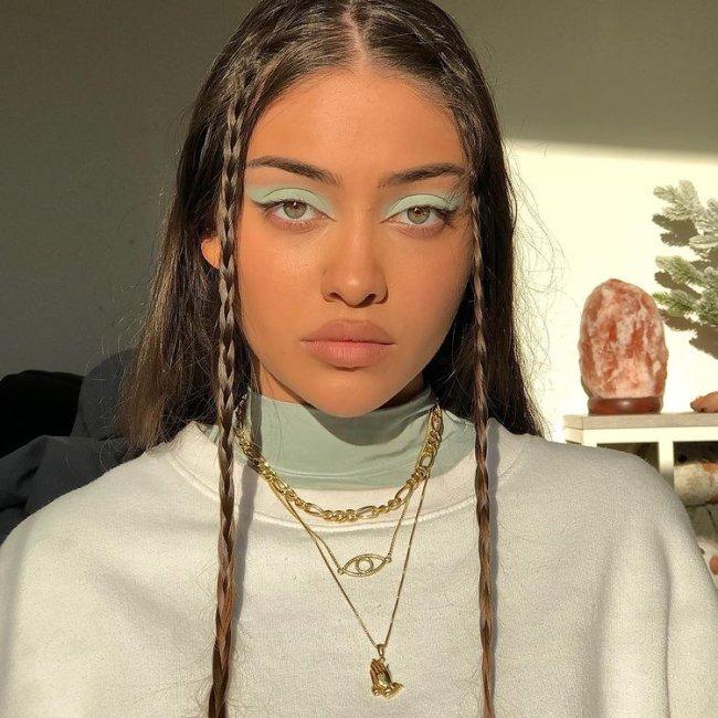 Selfie de uma mulher. Ela usa uma blusa verde menta de gola alta, casaco branco como sobreposição, colares dourados, maquiagem verde e tranças na franja. Ela olha para a câmera e não sorri.