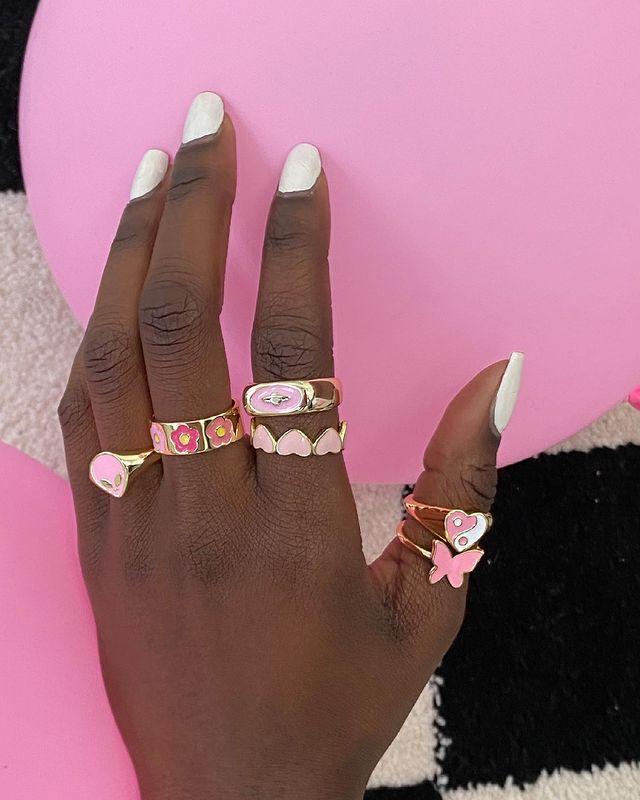 Foto de uma mão com diversos anéis dourados com detalhes em tons de rosa.