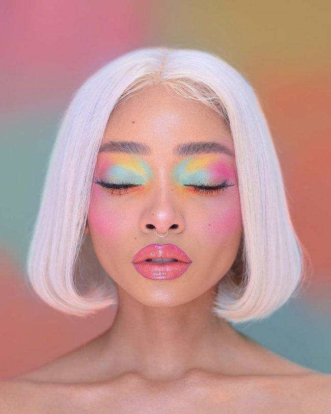Foto de uma mulher. Ela usa o cabelo curto solto, maquiagem com gloss, blush rosa marcado e sombra em tons de verde, rosa e amarelo pastel. Ela está de frente para a câmera, de olhos fechados e não sorri.