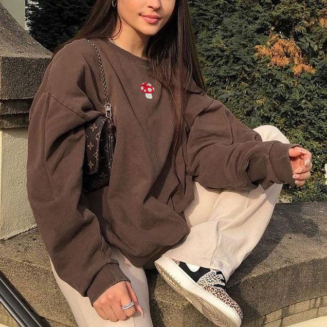 Foto de uma mulher sentada em um muro. Ela usa um moletom marrom com estampa de cogumelo, calça baggy cor creme, tênis e bolsa baguete. Ela olha para a câmera e sorri.