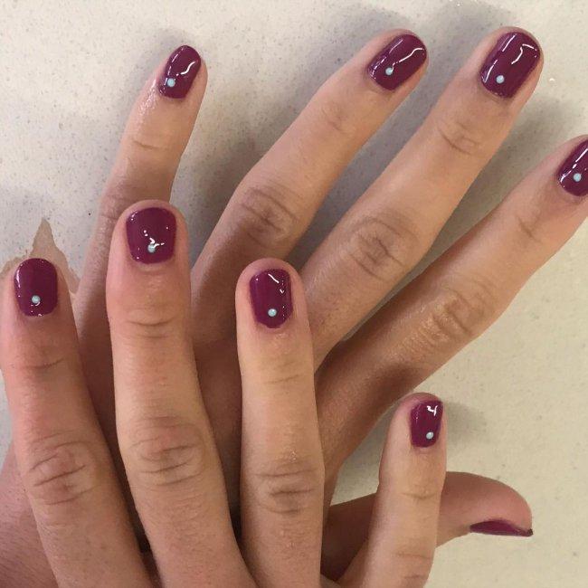Foto com destaque nas unhas com nail art de bolinha, dessa vez com fundo roxo e bolinha branca.