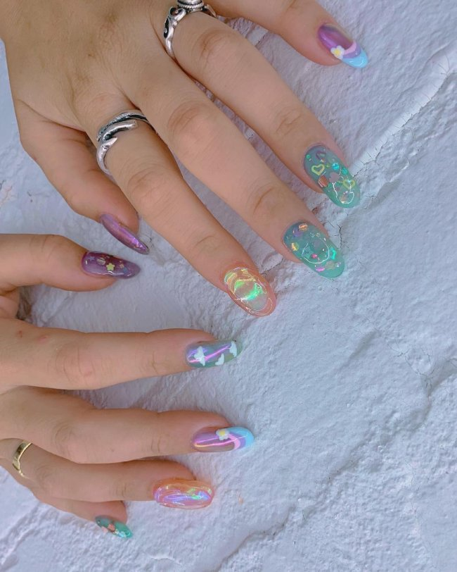 Foto com foco nas unhas, duas mãos expostas em mesa branca. Com nail art nas cores azul, amarelo, verde, e rosa.