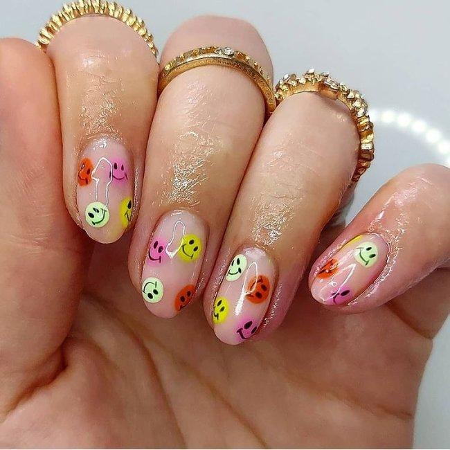 Foto com destaque nas unhas com nail art de bolinha, dessa vez formando smiles coloridos, nas cores laranja, roxo e verde.