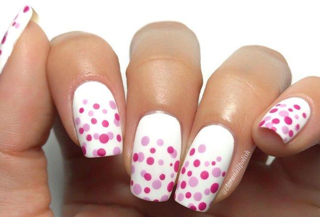 Foto com destaque nas unhas com nail art de bolinha, dessa vez com fundo branco e bolinhas em vários tons de rosa.