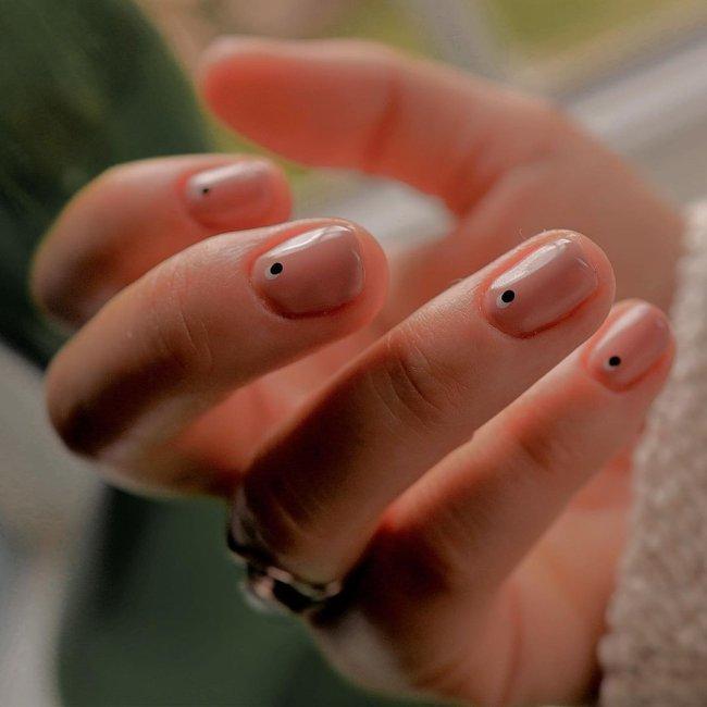 Foto com destaque nas unhas com nail art de bolinha, dessa vez nas cores preto e branca.