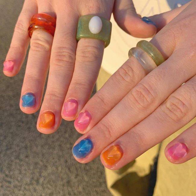 Foto com foco nas mãos, com esmalte colorido. Unhas laranja, rosa, azul e rosa. Com coração em 3D.