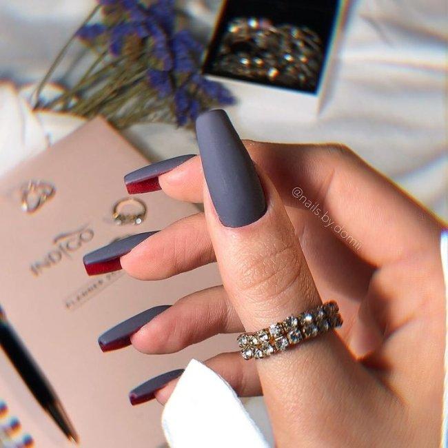 Foto com destaque para as mãos, exibindo unha flipside cinza com interior vermelho