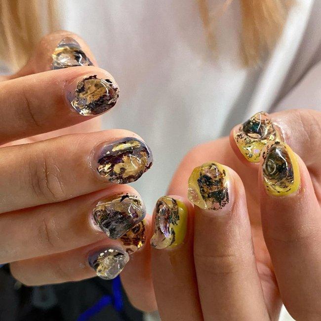 Foto com foco nas unhas com nail art com gel, amarela e preto.