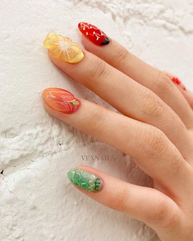 Foto com foco nas unhas com nail art em gel e relevo de frutas.