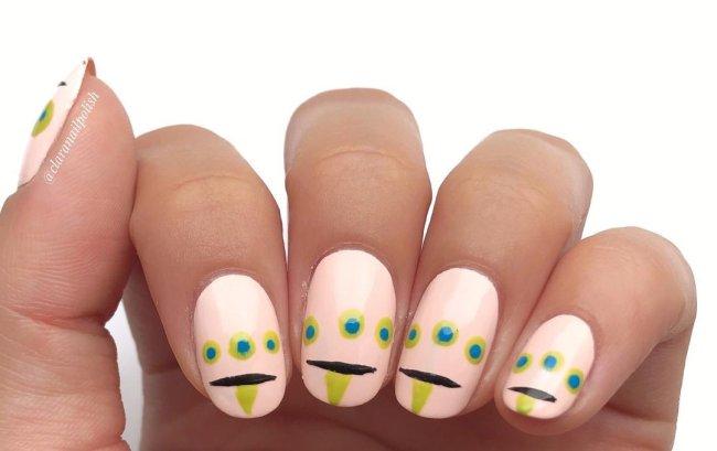 Foto com destaque nas unhas com nail art de bolinha, dessa vez formando um desenho de monstrinho com a língua para fora.