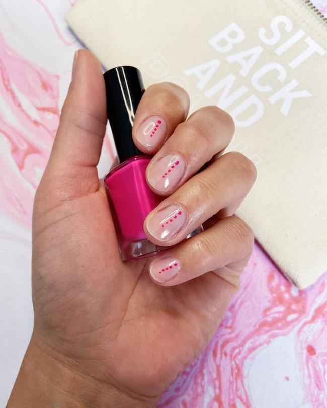 Foto com destaque nas unhas com nail art de bolinha, dessa vez com fundo transparente e bolinhas rosa.