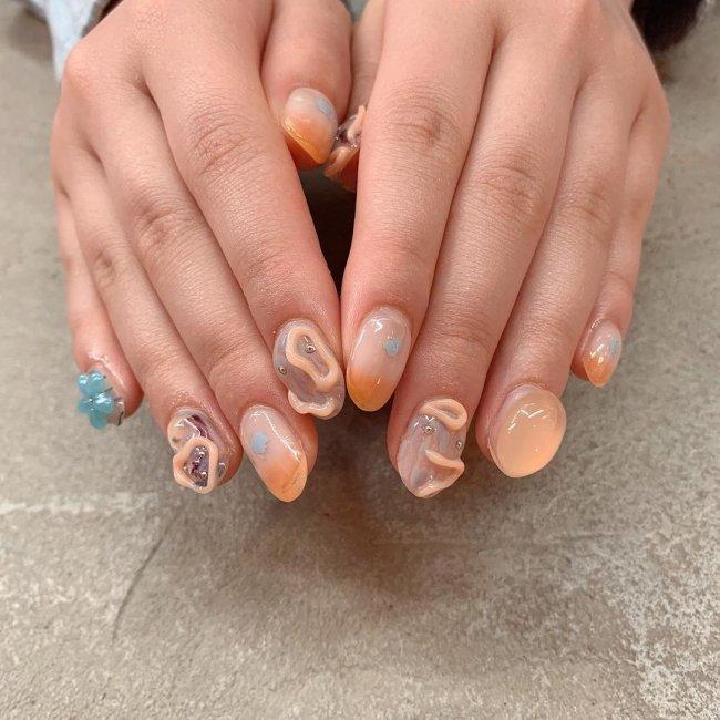 Foto com nail art com gel deixando relevo nas cores laranja e azul.