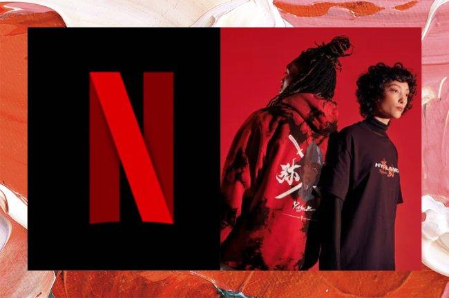 Montagem com a imagem do logo da Netflix na esquerda e na direita um homem de dreads de costa com um moletom vermelho e na frente dele, virada de lado, uma moça de cabelo curto e camisa preta. Eles estão em um fundo vermelho.