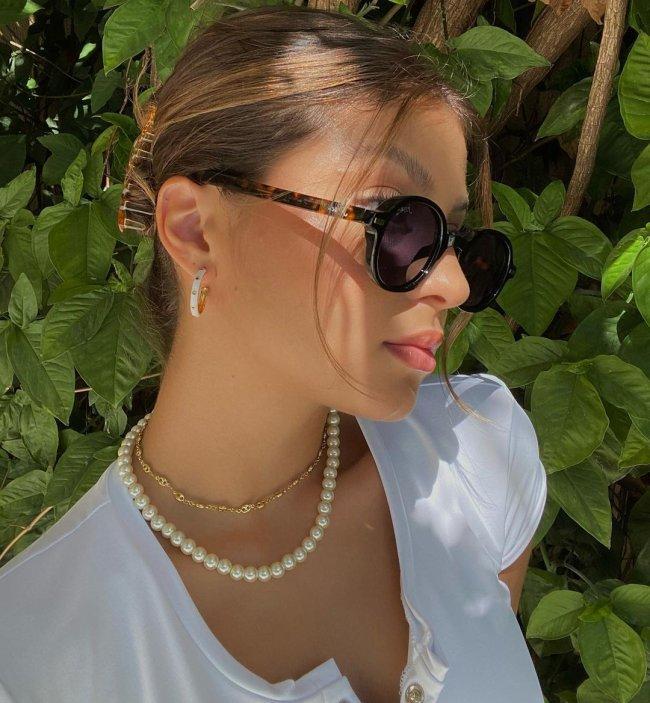 Selfie de uma garota com óculos de sol marrom de perfil. Ela usa uma blusa branca, colares, brinco de argola e cabelo preso em um coque.