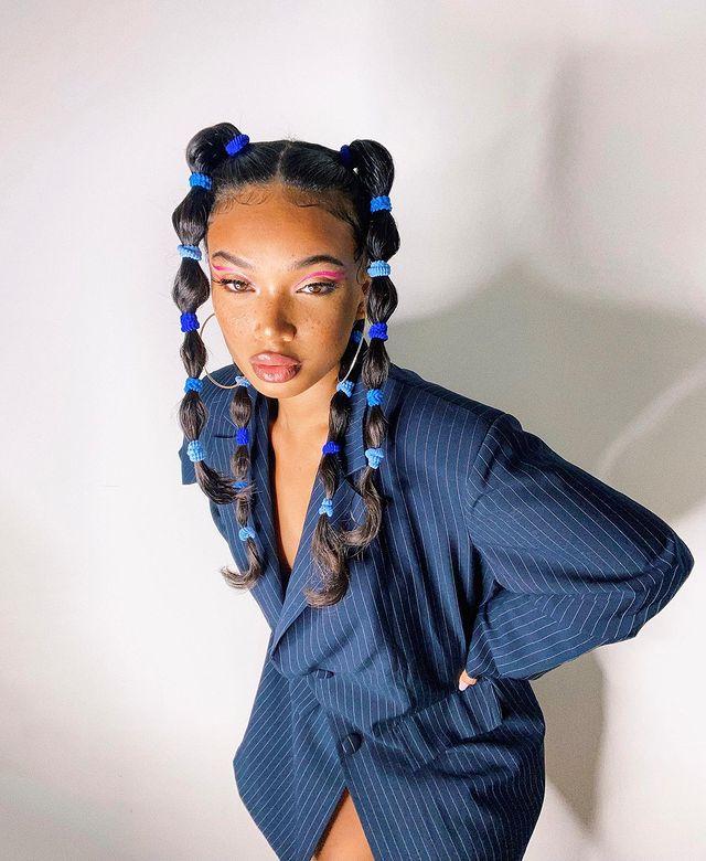 Foto de uma mulher em frente a uma parede branca. Ela usa um blazer azul com riscos brancos, cabelo preso em um penteado bolha dividido em quatro partes. Ela está com as mãos na cintura, olha para a câmera e não sorri.