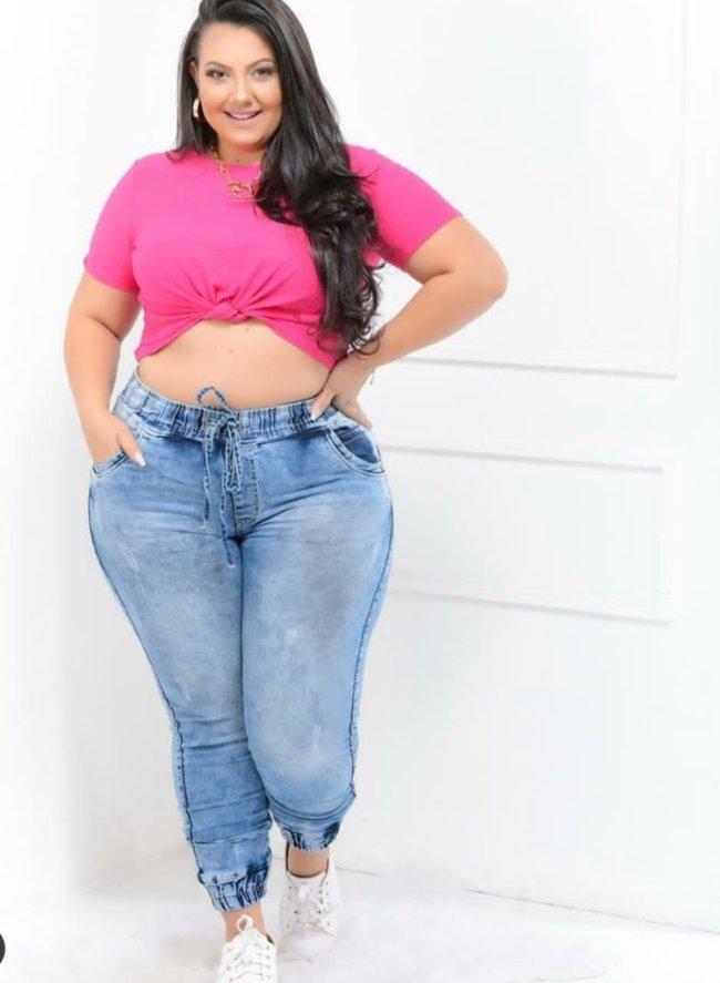 Jovem com blusa cropped rosa amarrada na barriga, usando calça jeans jogger com uma das mãos na cintura e expressão sorridente.