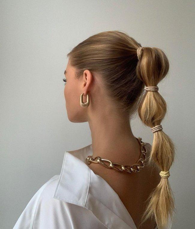 Foto de uma mulher de costas mostrando o penteado rabo de cavalo bolha. Ela usa uma camisa branca, colar e brincos dourados.
