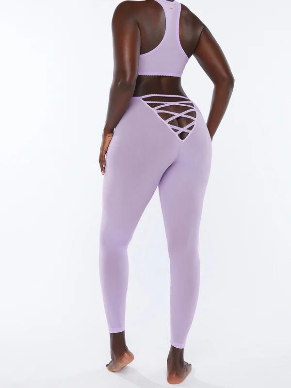 Modelo está de costas vestindo um top e uma calça legging esportiva na cor lilás. A calça possui um recorte em tiras no bumbum, deixando uma parte dele à mostra.