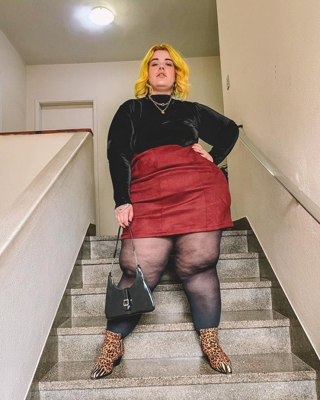 Foto de uma mulher em uma escada. Ela usa uma blusa preta de gola alta, saia de couro vermelha, meia calça, bota com estampa animal print e bolsa preta. Ela olha para a câmera e não sorri.