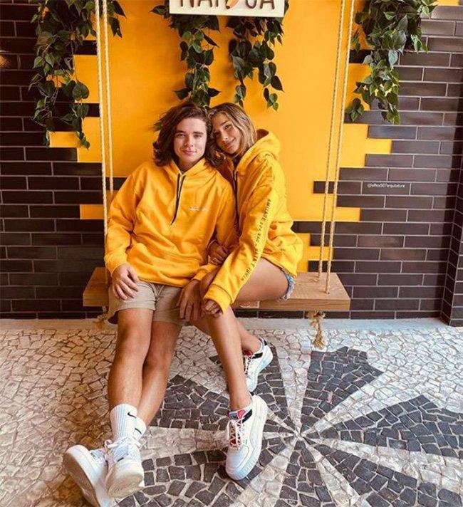 Casal sentado em balanço usando roupa combinando. Blusa de moletom amarela e short com tênis branco. Os dois aparecem sorridentes.