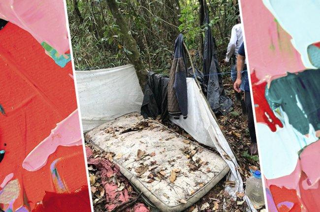 Imagem de um esconderijo na mata, com um colchão velha e um varal com algumas roupas penduradas