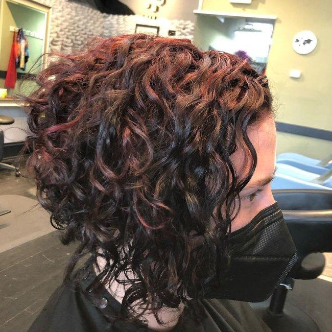 Mulher está de costas e não conseguimos ver seu rosto, somente seu cabelo com corte bob na cor ruiva e com assimetria.