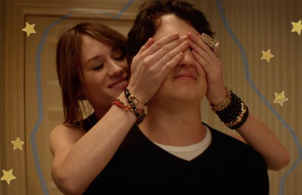Uma mulher sorrindo enquanto tapa os olhos do namorado com carinho, antes de fazer uma surpresa