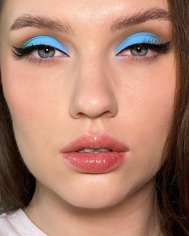 Jovem com expressão séria, a imagem foca em seu rosto com sombra azul e lábios com liptint.